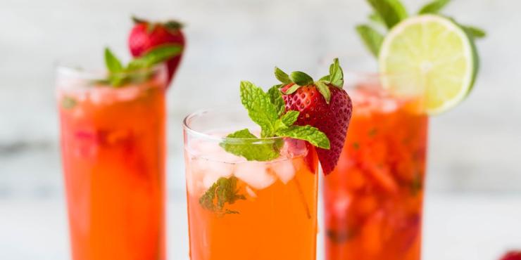 Varios refrescos de color rojo con frutas en el borde